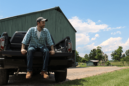 justin sitting in a truck on a farm
